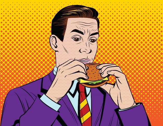 Chico adulto guapo en traje de almorzar con comida chatarra