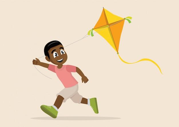 Chico africano jugando a la cometa.