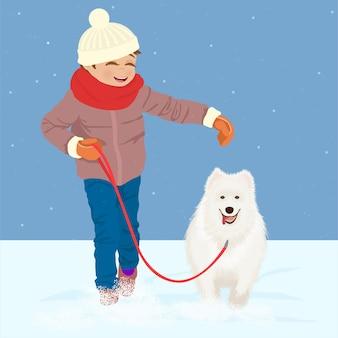 Chico corriendo con blanco su perro en la nieve