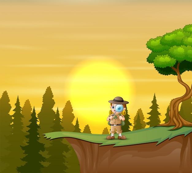 El chico explorador en el acantilado de la montaña.