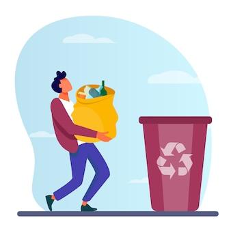 Chico joven bolsa de transporte con basura a la papelera