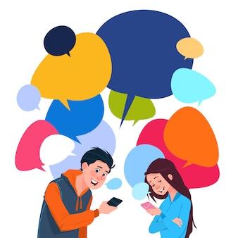 Chico joven y una niña de mensajería teléfonos celulares inteligentes sobre fondo colorido de burbujas de chat