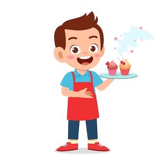 Chico lindo feliz intenta cocinar cupcake