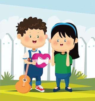 Chico lindo con guitarra y dando caja de corazón de chocolate una niña sobre valla blanca