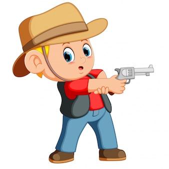 Chico lindo vestido de vaquero con revólver.