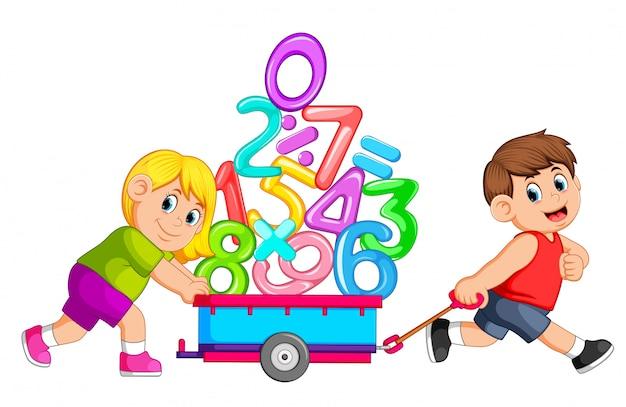 Chico tirando y chica empujando carro de numeros