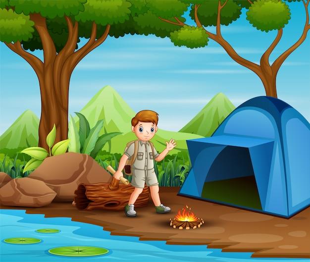 Chico en traje de explorador acampando en la naturaleza