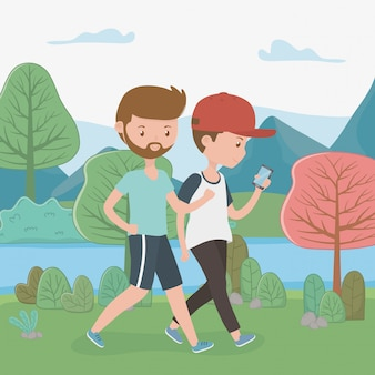 Chicos jóvenes caminando con teléfonos inteligentes en el parque