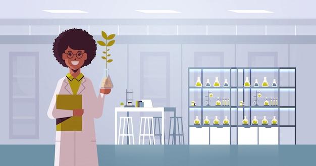 Científico femenino que examina la muestra de la planta en un tubo de ensayo