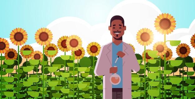 Científico hombre afroamericano con tubo de ensayo haciendo experimento en girasoles campo investigación ciencia agricultura agricultura concepto plano horizontal retrato