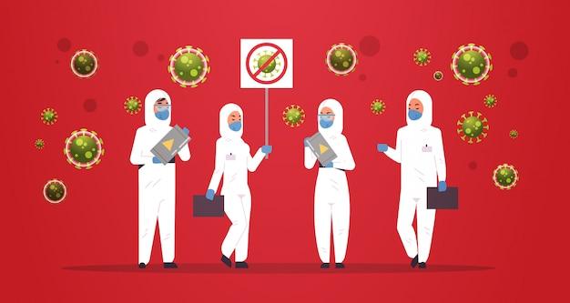 Científicos médicos en trajes de materiales peligrosos con pancarta de coronavirus de parada y barril con concepto de virus de epidemia de riesgo biológico wuhan pandemia riesgo de salud horizontal de longitud completa