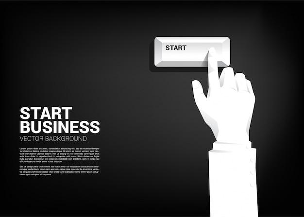 Cierre encima del botón del comienzo de la prensa de la mano del hombre de negocios