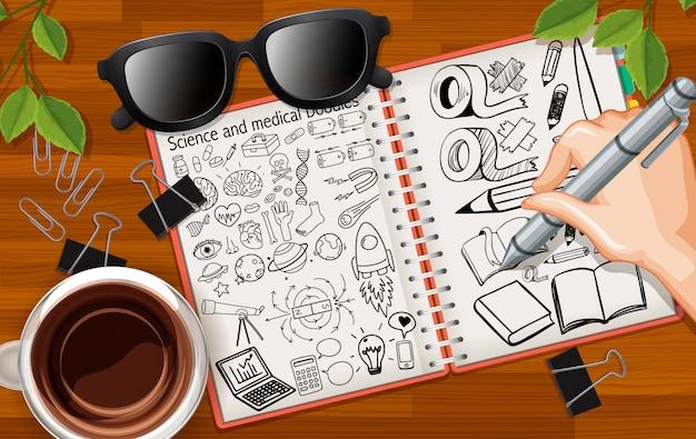 Ciérrese encima del dibujo de la mano inmóvil en el cuaderno con los vidrios y la taza de café en fondo del escritorio
