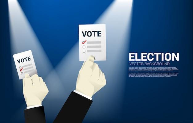 Ciérrese encima de la mano del hombre de negocios con la papeleta de voto para la elección.