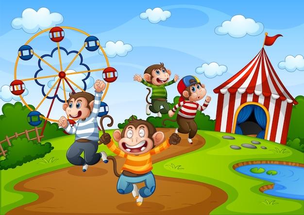 Cinco monitos saltando en la escena del parque de atracciones.