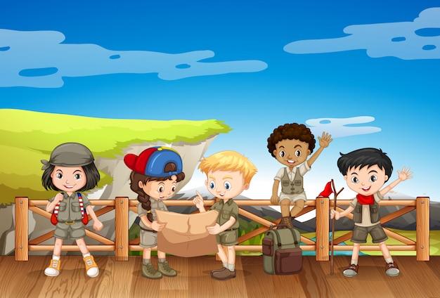 Cinco niños en traje de safari de pie en el puente