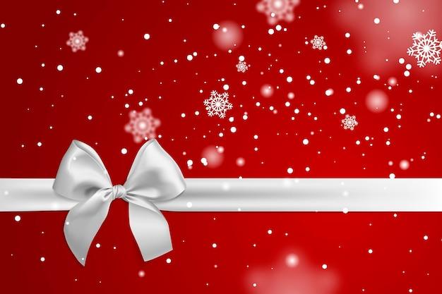 Cinta y lazo blanco realista aislado sobre fondo rojo con plantilla de nieve que cae