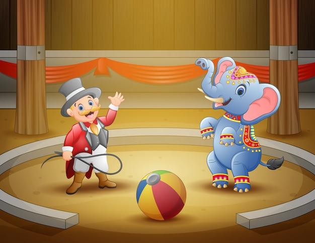 Circo ringmaster realiza un truco junto con el elefante en la arena