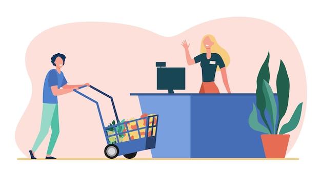 Cliente masculino rueda carrito de compras a la caja registradora