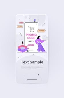 Clientes que usan un código de promoción de descuento en la pantalla del teléfono inteligente, compras en línea
