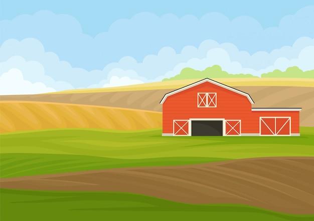Cobertizo de madera roja con garaje en un campo arado.