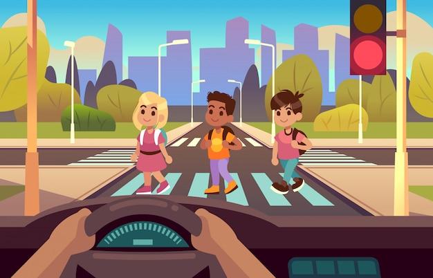 Coche dentro del cruce de peatones. manos del conductor en el panel de la rueda, niños cruzando la calle peatonal, parada, advertencia de luz