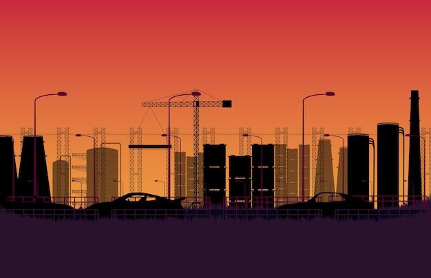 Coche de silueta en la carretera con la fábrica de construcción de la ciudad polígono industrial en gradiente naranja