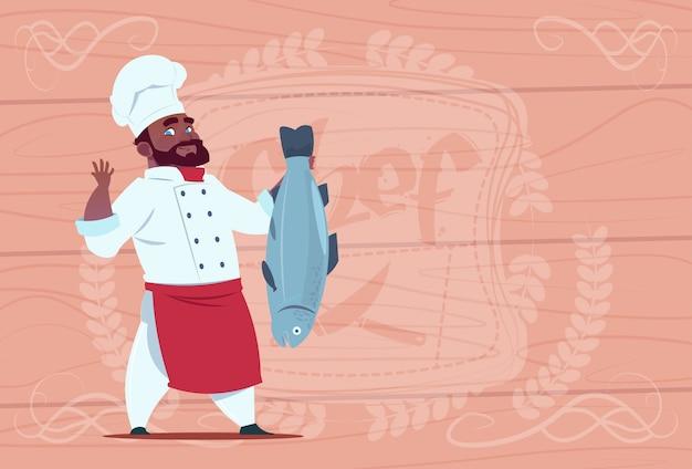 Cocinero afroamericano chef cocinar pescado sonriente restaurante de dibujos animados jefe en uniforme blanco sobre fondo con textura de madera