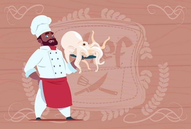 Cocinero afroamericano chef sostener pulpo sonriendo jefe de restaurante de dibujos animados con uniforme blanco sobre fondo con textura de madera