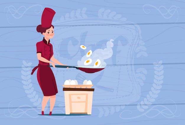 Cocinero chef mujer freír huevos jefe de dibujos animados en restaurante uniforme sobre fondo con textura de madera