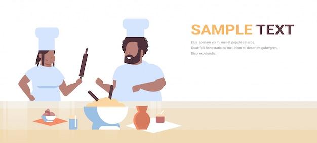 Cocineros par preparar comidas sabrosas hombre mujer chefs en uniforme cocinando juntos cocina moderna restaurante trabajadores equipo horizontal retrato copia espacio