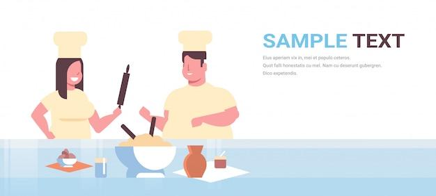 Cocineros par preparar comidas sabrosas hombre mujer chefs en uniforme cocinando juntos cocina moderna
