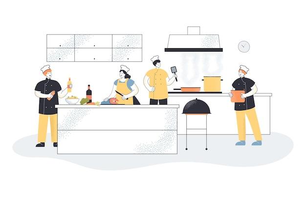 Cocineros profesionales que cocinan en cocina comercial