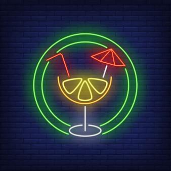 Cóctel de cítricos con paja y paraguas en círculo de neón