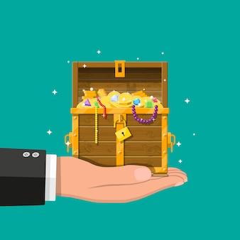 Cofre abierto lleno de tesoros en la mano