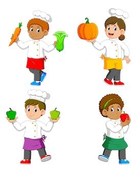 La colección del chef sosteniendo las verduras en sus manos.