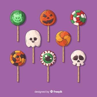 Colección de dulces de halloween dibujados a mano sobre fondo violeta