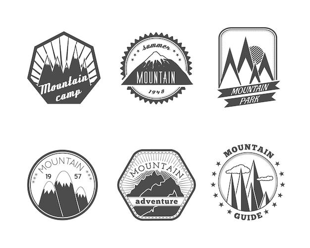 Una colección de etiquetas de campamento de verano de montañas nevadas redondas y poliangulares decorativos aislados ilustración vectorial