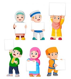Colección de niños musulmanes con gran cartel en blanco