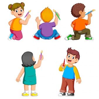 La colección de los niños que sostienen el pincel en sus manos.