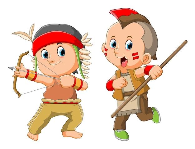 La colección de los niños usa el traje indio y sostiene el arma tradicional de la ilustración.