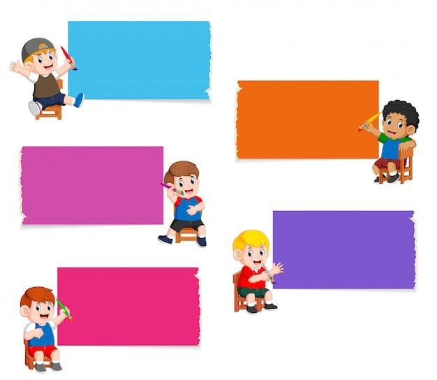 La colección del tablero en blanco en el color diferente con los niños que sostienen la pintura de pincel