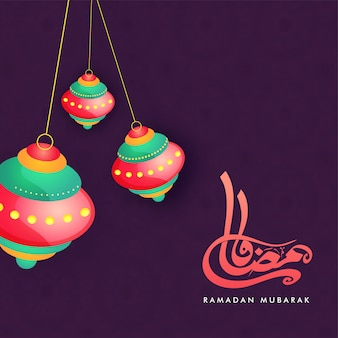 Colgantes linternas coloridas y texto caligráfico árabe ramadan mubarak sobre fondo púrpura.