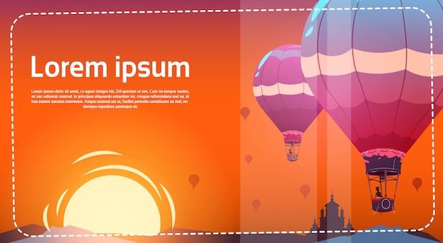 Coloridos globos de aire volando en el cielo sobre el paisaje del mar al atardecer