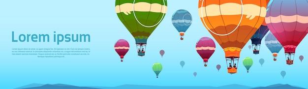 Coloridos globos de aire volando en el cielo sobre el paisaje de verano