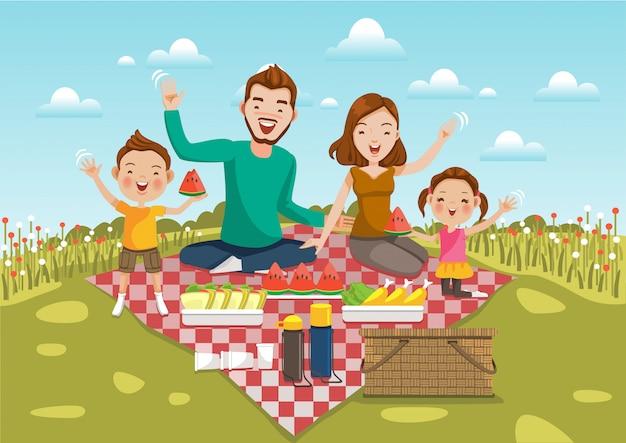 La comida campestre de la familia se sienta en un prado verde con el campo de flores y el cielo brillante.