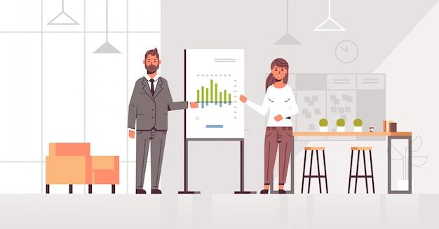 Compañeros de trabajo que presentan el gráfico financiero en el tablero de rotafolio pareja de negocios hombre mujer en seminario conferencia reunión haciendo presentación interior de la oficina moderna