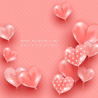 Composición con globos en forma de corazón volando en el aire sobre un fondo rosa de seda