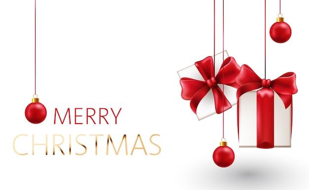 Composición navideña de caja de regalo colgante con cintas rojas