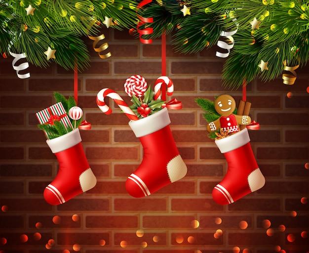 Composición navideña con calcetines festivos llenos de regalos y aguja de abeto con pared de ladrillo